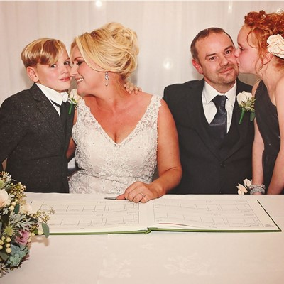 Bride & Groom signing the register with their children by their side.