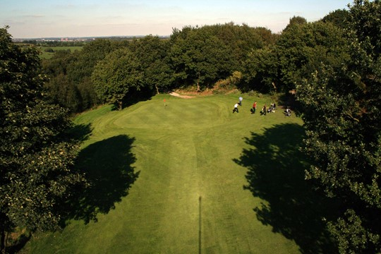Looking towards the 10th green from above surrounded by trees